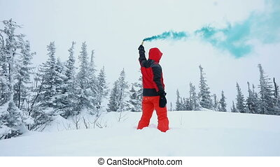 Young man playing with smoke flares on a top of mountains in winter forest
