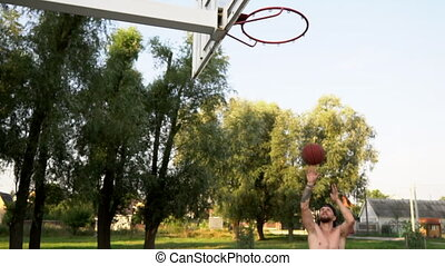 Young man plays basketball and throws the ball into the basket