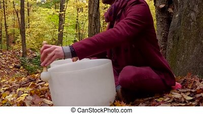 Fixed angle from the left side filmed in the forest and showing trees with leaves turned to yellow and dead leaves all around the white instruments. Man is wearing an urban red jacket.