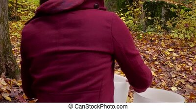 Traveling up from the back filmed in the forest and showing dead leaves all around the white instruments. Man is wearing an urban red jacket.