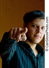 Young man pointing a finger to came