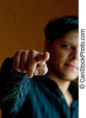 Young man pointing a finger to camera