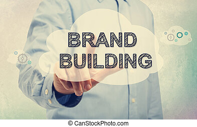Young man pointing at BRAND BUILDING