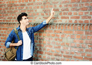 Young man pointing at copy space