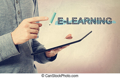 Young man pointing at E-Leaning text over tablet computer