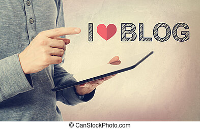 Young man pointing at I love Blog text over tablet computer