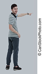 Young man pointing at something with his finger isolated on whit