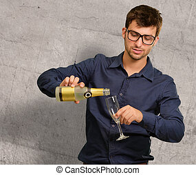 Young Man Pouring Champagne Into Glass