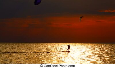 Young man practicing kitesurfing on the waves in the setting...
