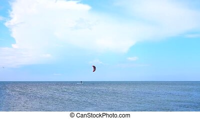 Young man practicing kitesurfing on the waves