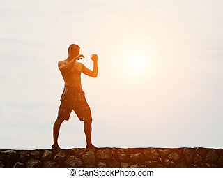 Young man practicing on the background of the sky, fighting