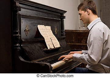 Young man practising at a piano