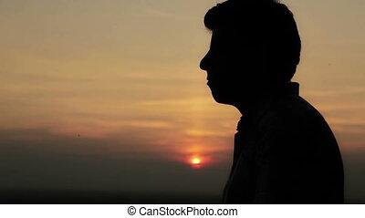 Young man praying at sunset