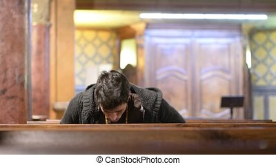 Young man sitting and kneeling in church praying