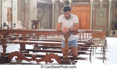 Young man sitting and kneeling in church praying