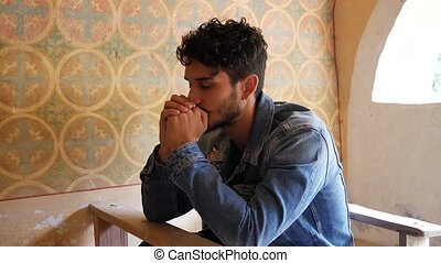 Young man praying in small chapel - Young man sitting and...