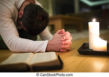 Young man praying, kneeling, Bible and candle next to him.