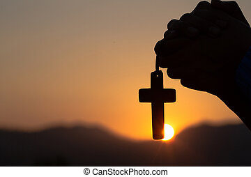 Young man praying With the Holy Cross in the morning