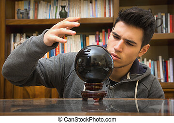 Young man predicting the future by looking into crystal ball...
