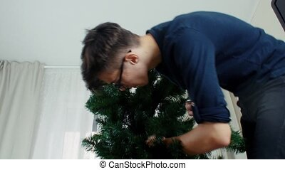 Young man preparing Christmas tree for decorations and having fun New year