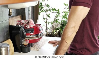 Young man preparing coffee with machine at home
