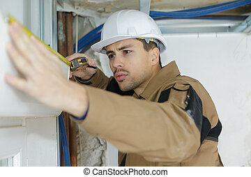 young man preparing to install cassette roller blinds on windows