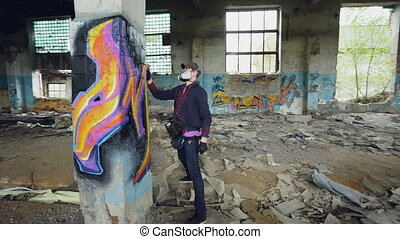 Young man professional graffiti painter is working inside...