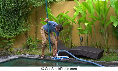 Young man professional swimming pool cleaner does pool...