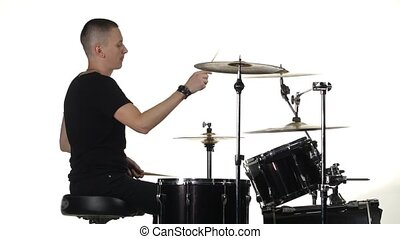 Young man professionally plays percussion instruments . White background. Side view
