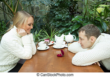 Young man proposing to girlfriend offering engagement ring. sitting in a cafe