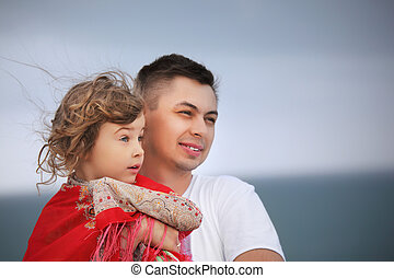 young man protects little girl from wind on seacoast