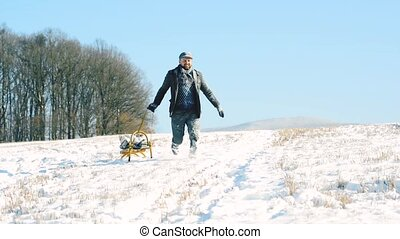 Young man pulling a sledge, running. Winter nature. - Young...