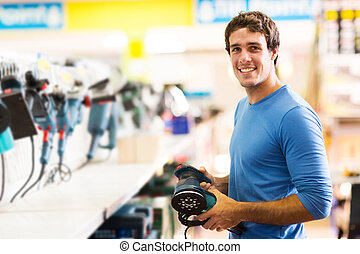 young man purchasing hand tool in hardware shop - smiling...