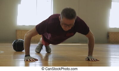 Young man pushes up from wooden floor in gym. He does it...