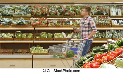 Young man pushing cart along the grocery aisles in the supermarket and using tablet pc to check shopping list.