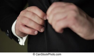 Young man put on classical suit black jacket indoors