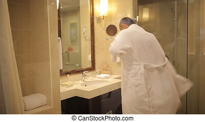 Young man puts on a bathrobe in the bathroom.