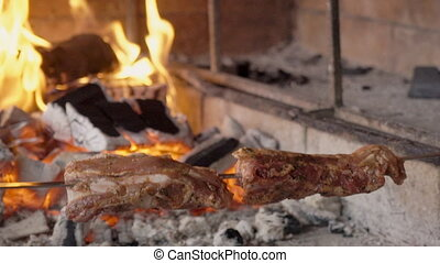 Young man puts skewers with meat on brazier outdoors. Male...