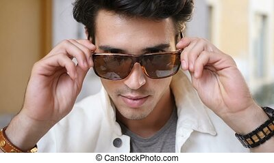 Young man putting on sunglasses looking at camera - Young...