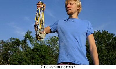 Young man raises a bundle of medals on a lake bank in summer