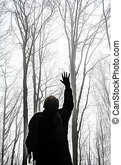 Young man reaching the sky in act of despair