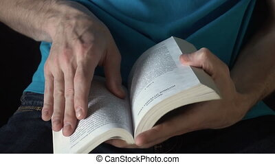 young man reading a book, leafing through pages, slow motion