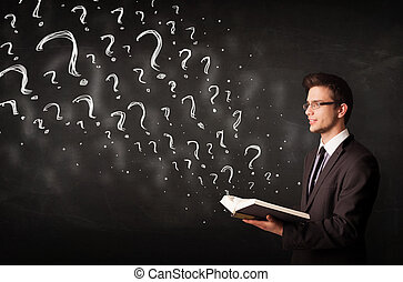 Young man reading a book with question marks coming out from it