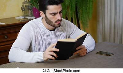 Young man reading book at home in his living-room