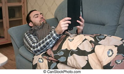 Young man reading book while lying sick on the sofa