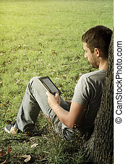 Young man reading e-book in the nature
