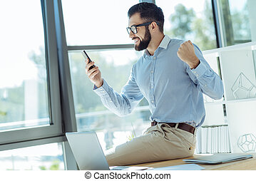 Young man reading good news on the phone at work