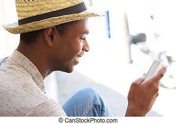 Young man reading text message on cell phone