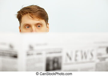 Young man reads the newspaper