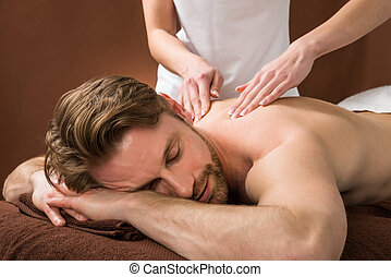Young Man Receiving Back Massage At Spa